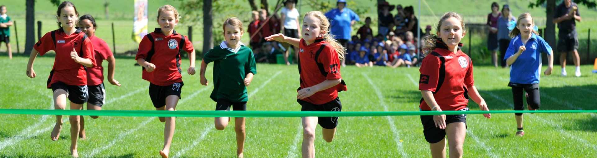 Young children cross the finish line during school sport